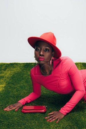 Photo pour Fille américaine africaine glamour dans la robe et le chapeau roses posant avec le sac sur l'herbe verte - image libre de droit