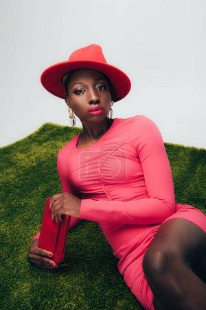 Photo pour Jeune femme américaine africaine élégante dans la robe et le chapeau roses posant avec le sac sur l'herbe verte - image libre de droit