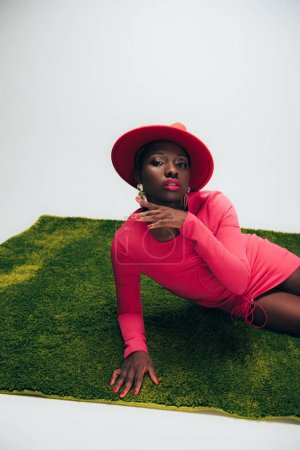 Photo pour Femme américaine africaine séduisante dans la robe et le chapeau roses posant sur l'herbe verte - image libre de droit
