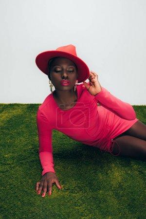 Photo pour Femme américaine africaine élégante dans la robe et le chapeau roses posant sur l'herbe verte - image libre de droit