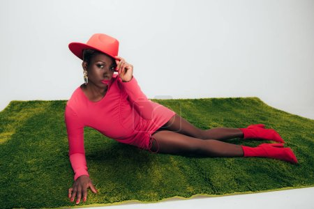 Photo pour Femme américaine africaine élégante dans la robe et le chapeau roses se trouvant sur l'herbe verte - image libre de droit