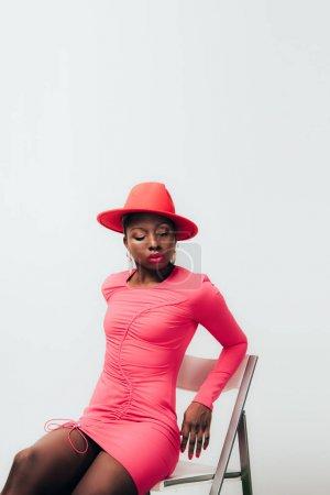 Photo pour Jeune Américaine africaine sensuelle en robe rose et chapeau posant sur chaise isolée sur blanc - image libre de droit