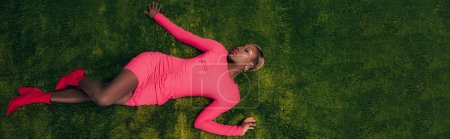 Photo pour Vue supérieure de la femme américaine africaine élégante dans la robe rose se trouvant sur l'herbe verte - image libre de droit