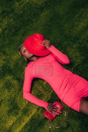 Photo pour Vue supérieure de belle femme américaine africaine dans la robe rose posant avec le chapeau et le sac sur l'herbe verte - image libre de droit