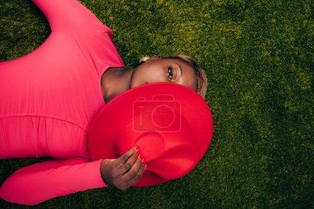 Photo pour Vue supérieure de la femme américaine africaine dans la robe rose posant avec le chapeau sur l'herbe verte - image libre de droit