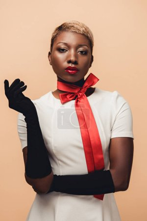 Photo for Young african american woman posing in white dress, red scarf and black gloves isolated on beige - Royalty Free Image