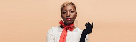 Photo pour Fille américaine africaine attirante à la mode posant dans l'écharpe rouge et les gants noirs d'isolement sur le beige - image libre de droit