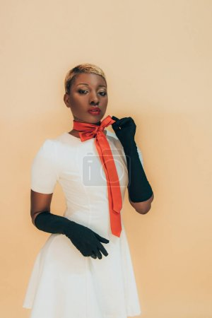 Photo for Stylish african american girl posing in trendy red scarf and black gloves isolated on beige - Royalty Free Image
