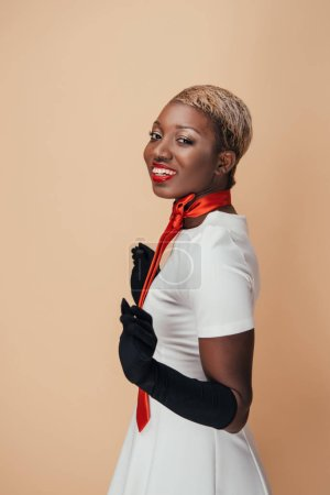 Photo for Cheerful african american woman posing in white dress, red scarf and black gloves isolated on beige - Royalty Free Image