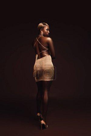 Photo pour Belle femme américaine africaine élégante élégante avec les cheveux courts posant dans la robe glamour sur le brun - image libre de droit