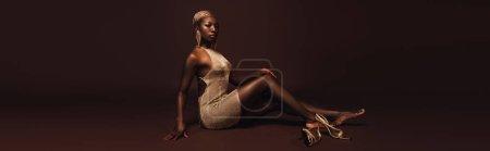 Photo pour Femme américaine africaine séduisante avec les cheveux courts posant dans la robe glamour sur le brun - image libre de droit