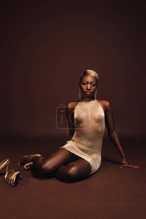 Photo for Attractive seductive african american woman with short hair on brown - Royalty Free Image
