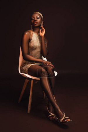 Foto de Attractive glamorous african american woman sitting on chair on brown - Imagen libre de derechos