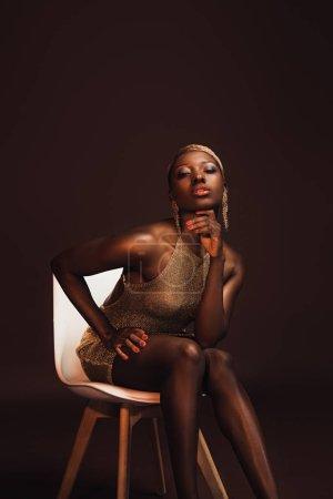 Photo pour Femme américaine africaine à la mode s'asseyant sur la présidence d'isolement sur le brun - image libre de droit