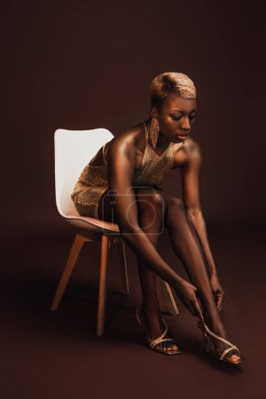 fashionable african american woman with short hair sitting on chair on brown
