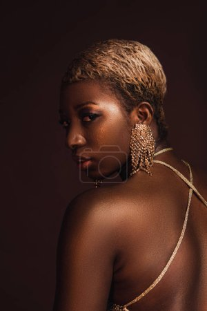 Photo for Beautiful fashionable african american woman with short hair isolated on brown - Royalty Free Image