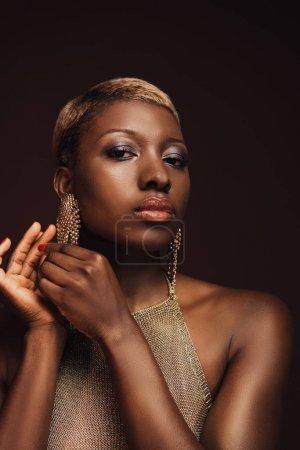 Photo pour Belle femme afro-américaine de glamour avec des boucles d'oreilles d'isolement sur le brun - image libre de droit