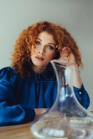 Photo for Beautiful stylish redhead woman posing near glass vase isolated on grey - Royalty Free Image