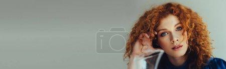 Photo pour Plan panoramique de belle rousse jeune femme regardant la caméra sur gris avec espace de copie - image libre de droit