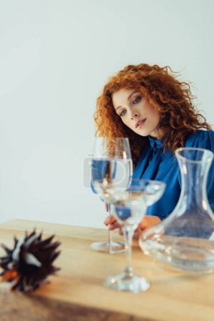 attractive stylish redhead woman posing near table with glasses of water isolated on grey