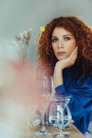 Foto de Atractiva mujer pelirroja elegante posando cerca de gafas en gris - Imagen libre de derechos