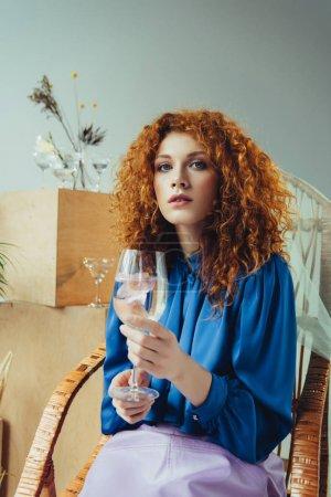 Photo pour Belle femme élégante de rousse retenant le verre avec la fleur - image libre de droit