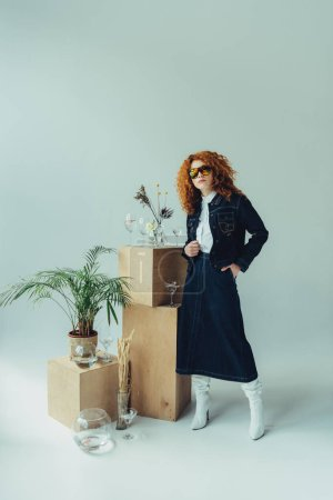 stylish redhead girl posing near wooden boxes, glasses and plants on grey