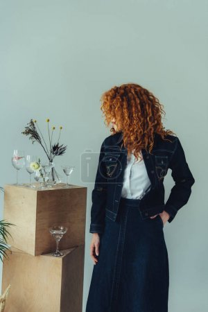 stylish redhead girl posing near wooden boxes, glasses and plants isolated on grey
