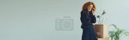 Foto de Foto panorámica de la chica pelirroja con estilo posando cerca de vasos y plantas aisladas en gris con espacio de copia - Imagen libre de derechos