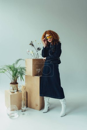 stylish redhead girl in sunglasses posing near boxes, glasses and plants on grey