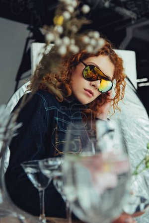 Photo for Selective focus of stylish redhead woman in sunglasses posing near glasses and dried flowers - Royalty Free Image