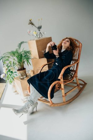 Photo for Stylish laughing girl in wicker chair with film camera near wooden boxes, glasses and plants on grey - Royalty Free Image