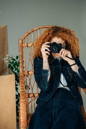 Photo pour Femme élégante de rousse dans la présidence en osier prenant la photo avec l'appareil-photo de film sur le gris - image libre de droit