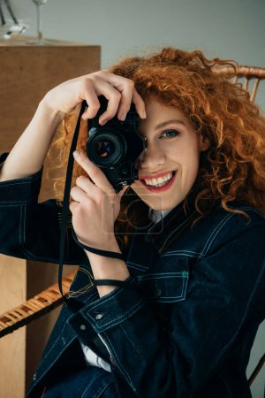 Photo for Smiling stylish redhead woman in wicker chair taking photo with film camera isolated on grey - Royalty Free Image
