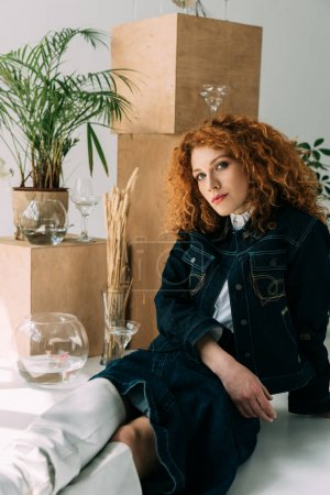Photo for Trendy redhead girl sitting and posing near wooden boxes, glasses and plants on grey - Royalty Free Image