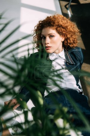 Photo for Selective focus of stylish redhead girl posing near green leaves - Royalty Free Image