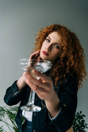 Photo for Beautiful stylish redhead woman posing with glass on grey - Royalty Free Image