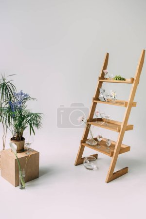 Photo pour Verres avec de l'eau et des fleurs sur échelle en bois près pot de fleurs sur boîte sur gris - image libre de droit