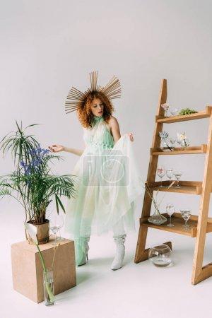 Foto de Elegante pelirroja chica en vestido con accesorio en la cabeza posando cerca de la escalera con flores y gafas - Imagen libre de derechos
