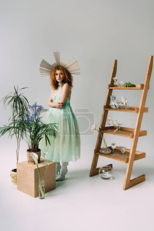 Photo for Stylish redhead girl in dress with accessory on head posing near ladder with flowers and glasses - Royalty Free Image