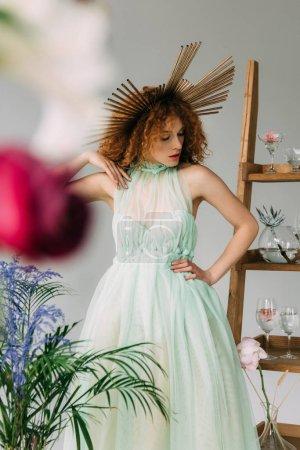Photo pour Foyer sélectif de la fille élégante de rousse avec l'accessoire sur la tête posant près de l'échelle avec des fleurs et des glaces - image libre de droit