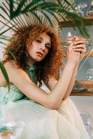 Photo pour Fille rousse à la mode avec accessoire sur la tête dans la robe posant près de l'usine - image libre de droit
