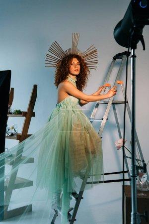 beautiful stylish girl with accessory on head posing on ladder near photographic lightning
