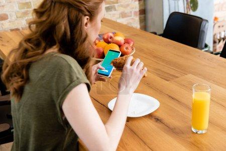 Photo pour KYIV, UKRAINE - 8 MAI 2020 : Vue de côté de la femme utilisant un smartphone avec application twitter tout en mangeant croissant à table - image libre de droit