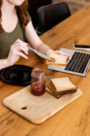 Ausgeschnittene Ansicht einer Frau, die Marmelade auf Toast in der Nähe von Gadgets auf Holztisch gießt