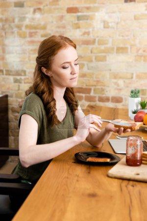 Photo pour Concentration sélective de la femme ajoutant de la confiture sur les toasts près des appareils numériques et des fruits sur la table - image libre de droit