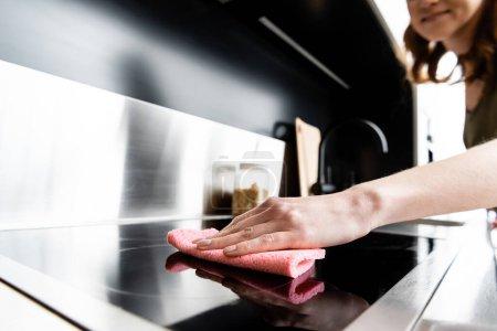Photo pour Vue recadrée du poêle de nettoyage femme avec chiffon dans la cuisine - image libre de droit