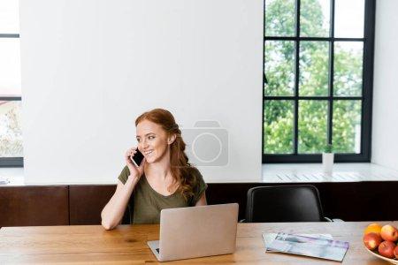 Photo pour Belle femme souriante tout en parlant sur smartphone près d'un ordinateur portable, magazines et fruits sur la table - image libre de droit