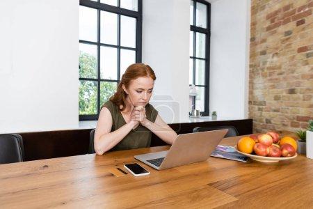 Photo pour Femme regardant ordinateur portable près de la carte de crédit, smartphone et fruits sur la table à la maison - image libre de droit