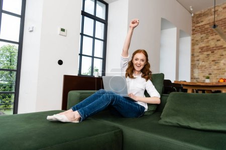 Photo pour Femme positive montrant un geste oui tout en tenant un ordinateur portable sur le canapé - image libre de droit